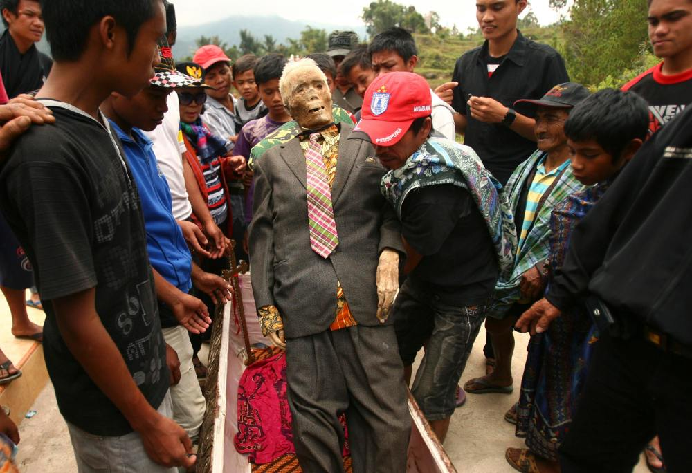 A man holds up a mummy before relatives give it new clothes in a ritual in the Toraja district of Indonesia's South Sulawesi Province